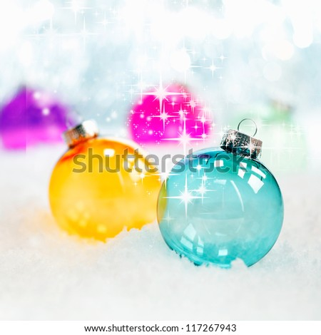 Sparkling twinkling colourful translucent glass Christmas baubles in fresh winter snow with bokeh of soft white lights, square format - stock photo