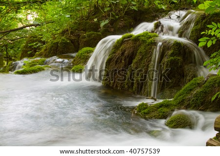 Sparkling waterfall between the green vegetation - stock photo