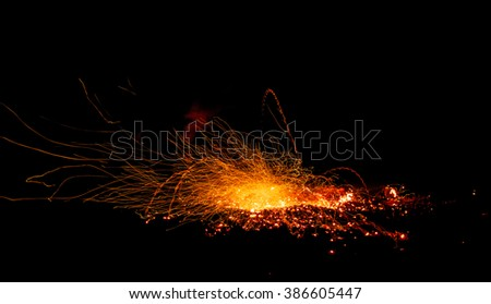 Sparks fire and the trajectory of falling embers from the explosion. The photo was taken at night on slow shutter speeds - stock photo