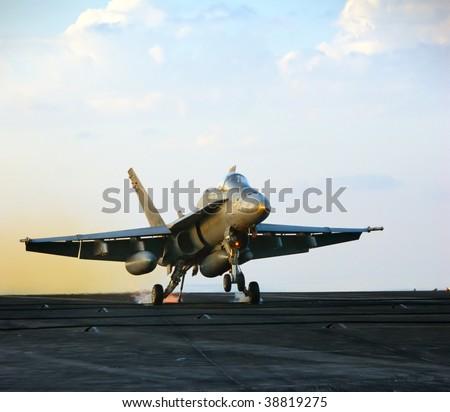 Sparks fly as an F-18 Hornet lands aboard an aircraft carrier - stock photo