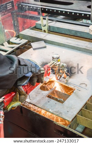 sparks flying over the working table during metal grinding - stock photo