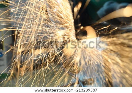 sparks frying over the working table during metal grinding  - stock photo