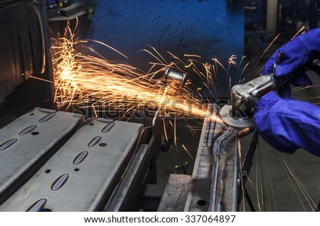 Sparks movement while grinding iron in factory - stock photo