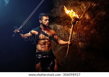 spartan on a dark background rocks, warrior, fighte holds a raised sword and burning torch, spartan looking ahead, black leather bandage on hips, athletic body. - stock photo