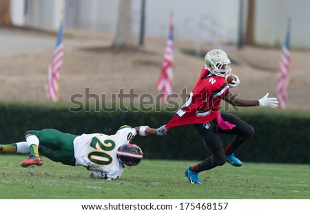 SPARTANBURG, SC - DEC 21, 2013 Future Clemson RB #2 Jae'lon Oglesby brakes the tackle of North Carolina LB #20 Cody Pudie during the Shrine Bowl all-star game - stock photo