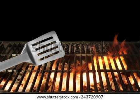 Spatula on the Flaming BBQ Grill. Black background. You can see more BBQ and Picnic scene in my public set. - stock photo