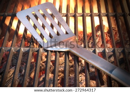 Spatula On The Hot Empty Clean Flaming Grill Close-up. Summer Outdoor Backyard Barbecue Party or Cookout or Picnic Concept. - stock photo
