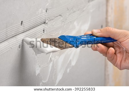 spatula with plaster in hand, closeup - stock photo
