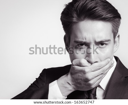 Speak no evil concept - face of businessman covering his mouth - stock photo