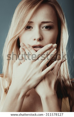 Speak no evil concept. Surprised woman face covering her mouth with hands close up - stock photo