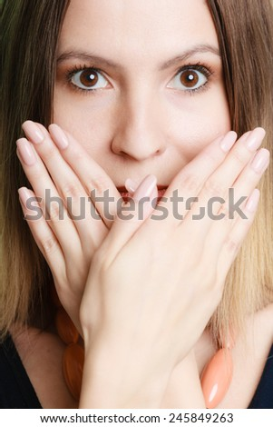 Speak no evil concept. Surprised woman face wide eyed covering her mouth with hands - stock photo