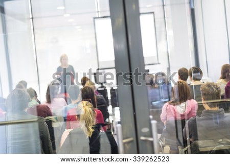 Speaker Giving a Talk at Business Meeting. Audience in the conference hall. Business and Entrepreneurship. Trough the glass door look. - stock photo