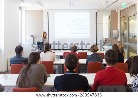 Speaker giving presentation in lecture hall at university. Participants listening to lecture and making notes. Copy space for brand on white screen. - stock photo