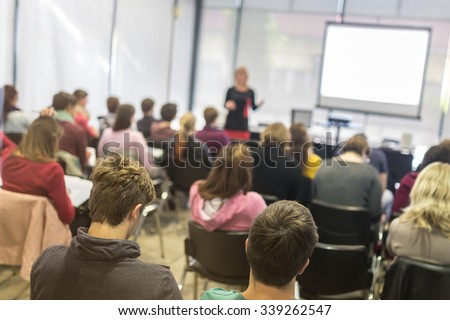Speaker giving presentation in lecture hall at university. Participants listening to lecture and making notes.  Trough the glass rear view of audience in lecture room. - stock photo