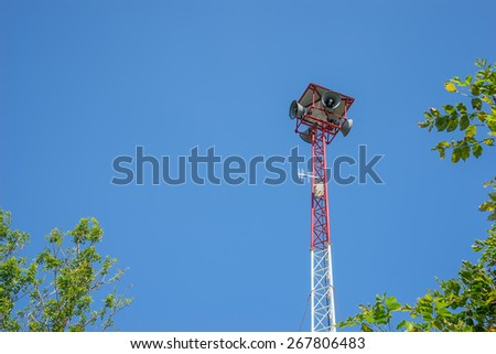Speaker on high tower and clear blue sky with tree as a foreground - stock photo