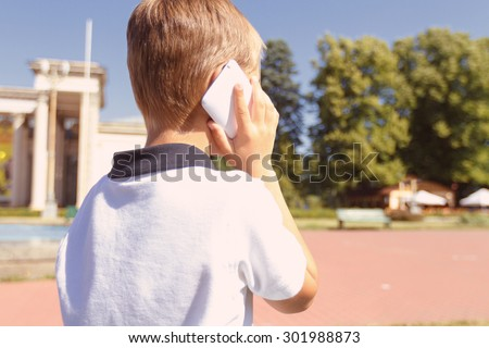 Speaking with granny. Back view of little boy talking per mobile phone outside - stock photo