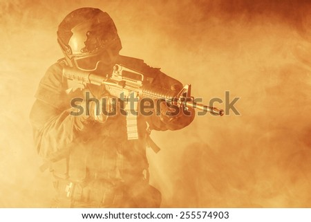 Spec ops police officer SWAT in the smoke and fire - stock photo