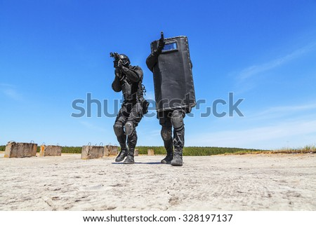 Spec ops police officers SWAT with ballistic shield in action - stock photo