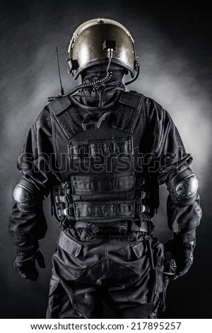 Spec ops soldier on black background shot from behind - stock photo