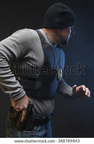 Special agent looking at suspect during a studio shoot.  Undercover Law Enforcement Officer with weapon. - stock photo