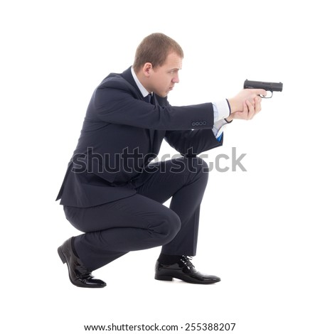 special agent man in business suit sitting and shooting with gun isolated on white background - stock photo