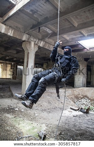 Special forces operator during assault rappeling with weapons - stock photo