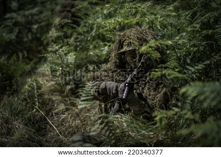 Special forces soldier during change of ammunition clip. - stock photo
