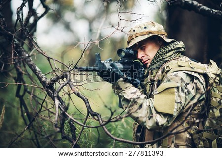 Special forces soldier with rifle in the forest - stock photo