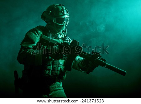 Special forces soldier with rifle in the smoke - stock photo