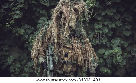 Special soldier in camouflaged sniper suit before action. Photo edited into warfare look and dark atmosphere. Selective focus. - stock photo