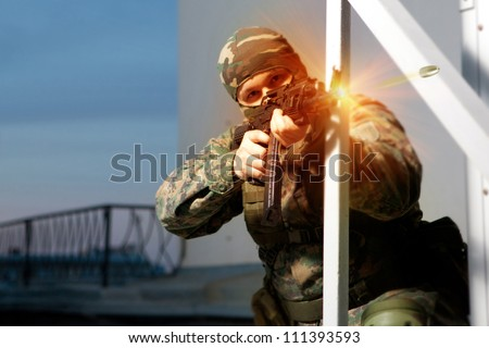 Special squad soldier is shooting from the Kalashnikov machine gun. - stock photo