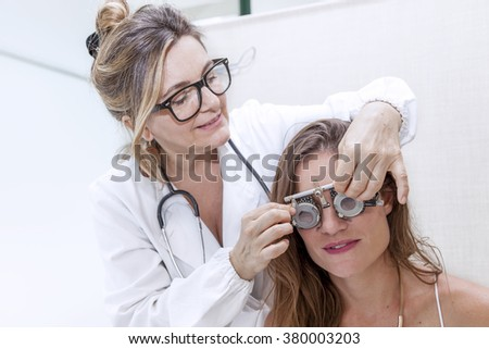 specialist in ophthalmology test new lenses on a patient with phoropter  - stock photo