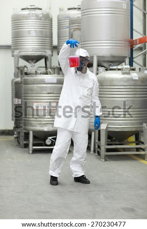 Specialist in protective uniform examining sample - stock photo