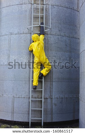 specialist in protective uniform going up a metal ladder on storage tank - stock photo