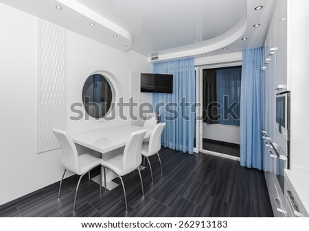 Specious modern white blue interior kitchen-dining room with the built-in household appliances and the TV - stock photo