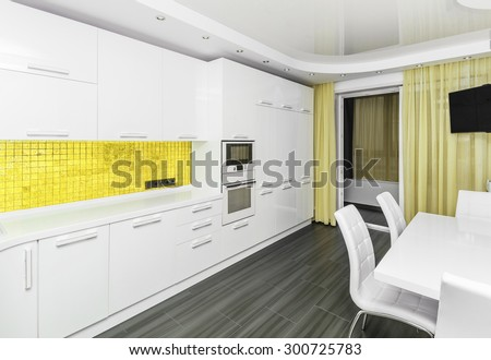 Specious modern white yellow interior kitchen-dining room with the built-in household appliances and the TV - stock photo