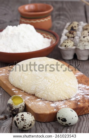 speckled quail eggs and flour on a rustic wooden background - stock photo