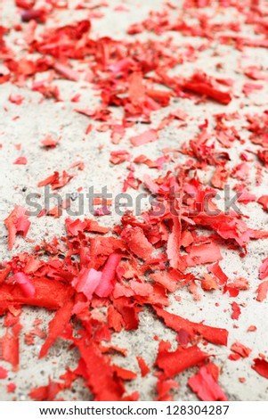 Specks of red paper on the floor from burnt firecrackers - stock photo