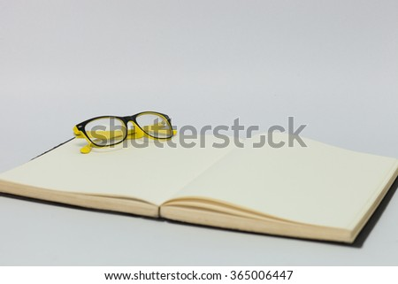 Spectacles on book with white background - stock photo