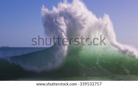 Spectacular backwash from the  Indian Ocean waves breaking on basalt rocks at  Ocean beach Bunbury Western Australia on a sunny morning in early winter  sends salty spray high into the air. - stock photo