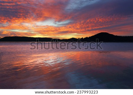 Spectacular colours pre sunrise at Koolewong overlooking the oyster farms.  Motion in water - stock photo