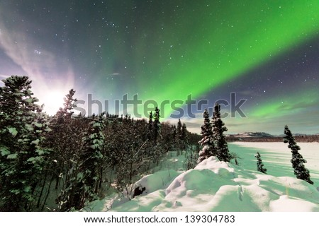 Spectacular display of intense Northern Lights or Aurora borealis or polar lights forming green swirls and moon behind ice fogs over snowy winter taiga landscape of Yukon Territory  Canada - stock photo