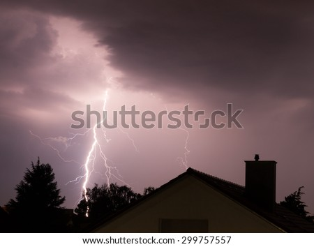 Spectacular lightning strikes a house in an urban area on stormy summer evening - stock photo
