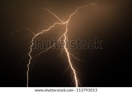Spectacular orange colored lightning strike in the night with no buildings or trees - stock photo