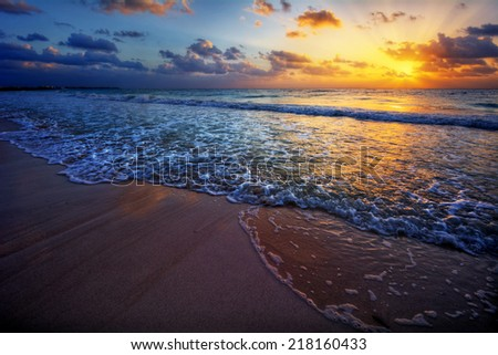 Spectacular sandy beach sea side vacation destination sunrise with colorful sky and clouds - stock photo