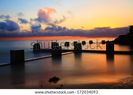Spectacular sunrise at the Coogee Baths, south side, Coogee, Australia.  The sun lit up the summer sky.  Long exposure. - stock photo