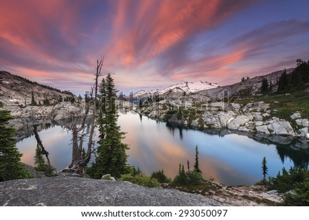 Spectacular sunrise with pink clouds over an alpine lake - stock photo
