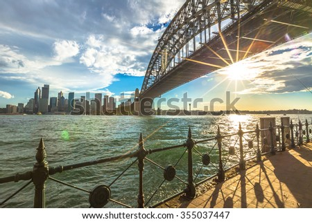 Spectacular Sydney Skyline at sunset. Walking on the path that leads beneath the Sydney Harbour Bridge, New South Wales, Australia. - stock photo