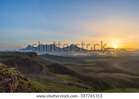 Spectacular view of a sunrise from El Oso viewpoint in the Gran Sabana region, at Canaima National Park, Venezuela. The tepuis (table-top mountains) of the eastern chain are visible on the background. - stock photo