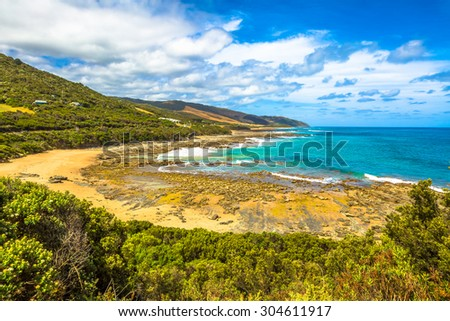 Spectacular view of the Great Ocean Road with its famous mountains, the winding road, cliffs, rocky beaches, the turquoise sea and its waves for surfing. - stock photo